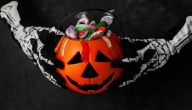 Jack O' Lantern, trick or treat bucket, filled with candies held by a skeleton hands on black background. Halloween celebration concept.