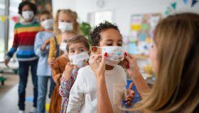 Pre school teacher helping little multiracial boy to wear face mask indoors at nursery school, coronavirus concept.