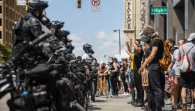 Protesters confront police officers standing in the middle...
